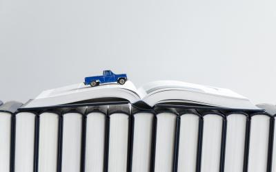 Matchbox car driving over an open book