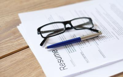 Resume on a table with a pen and glasses