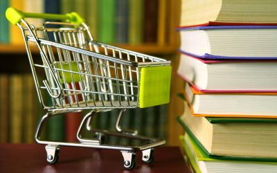 Tiny shopping cart next to a stack of books