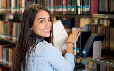 Girl smiling and shelving books