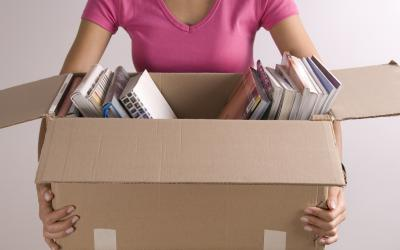 Woman holding a box partially filled with books