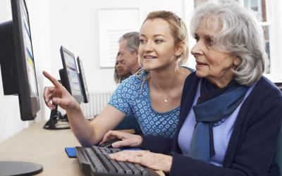 Woman getting computer help from another