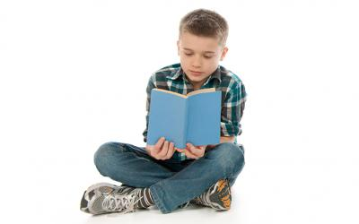 Boy sitting cross-legged reading a book