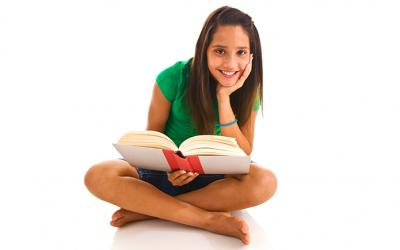 Teenager holding a book and smiling