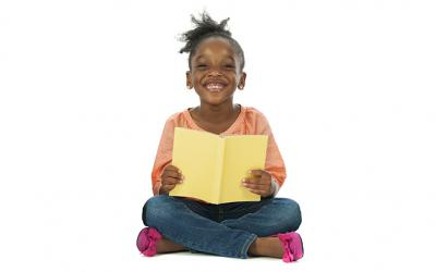 Girl holding a book and smiling